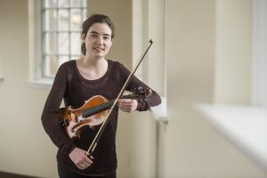 Erin Gartland '17 holds a violin and bow