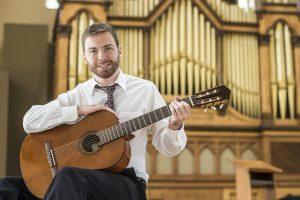 John Bradley holding a guitar in the chapel