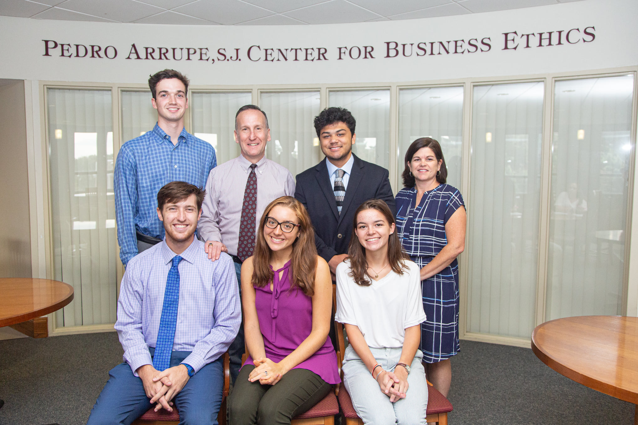 The student and faculty team from the Arrupe center pose in front of the sign.
