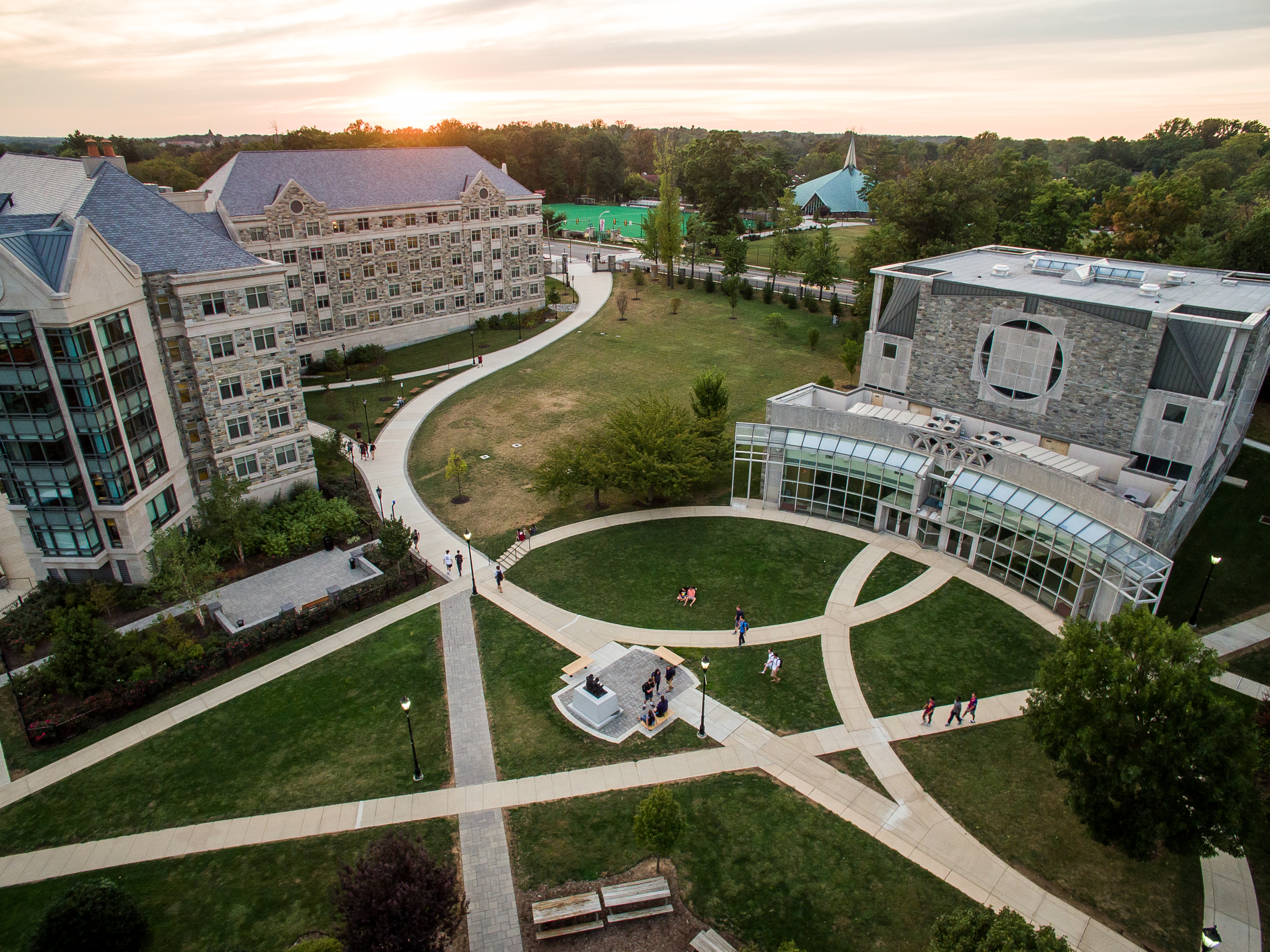 An aerial shot of campus shows the pathways between buildings at sunset.