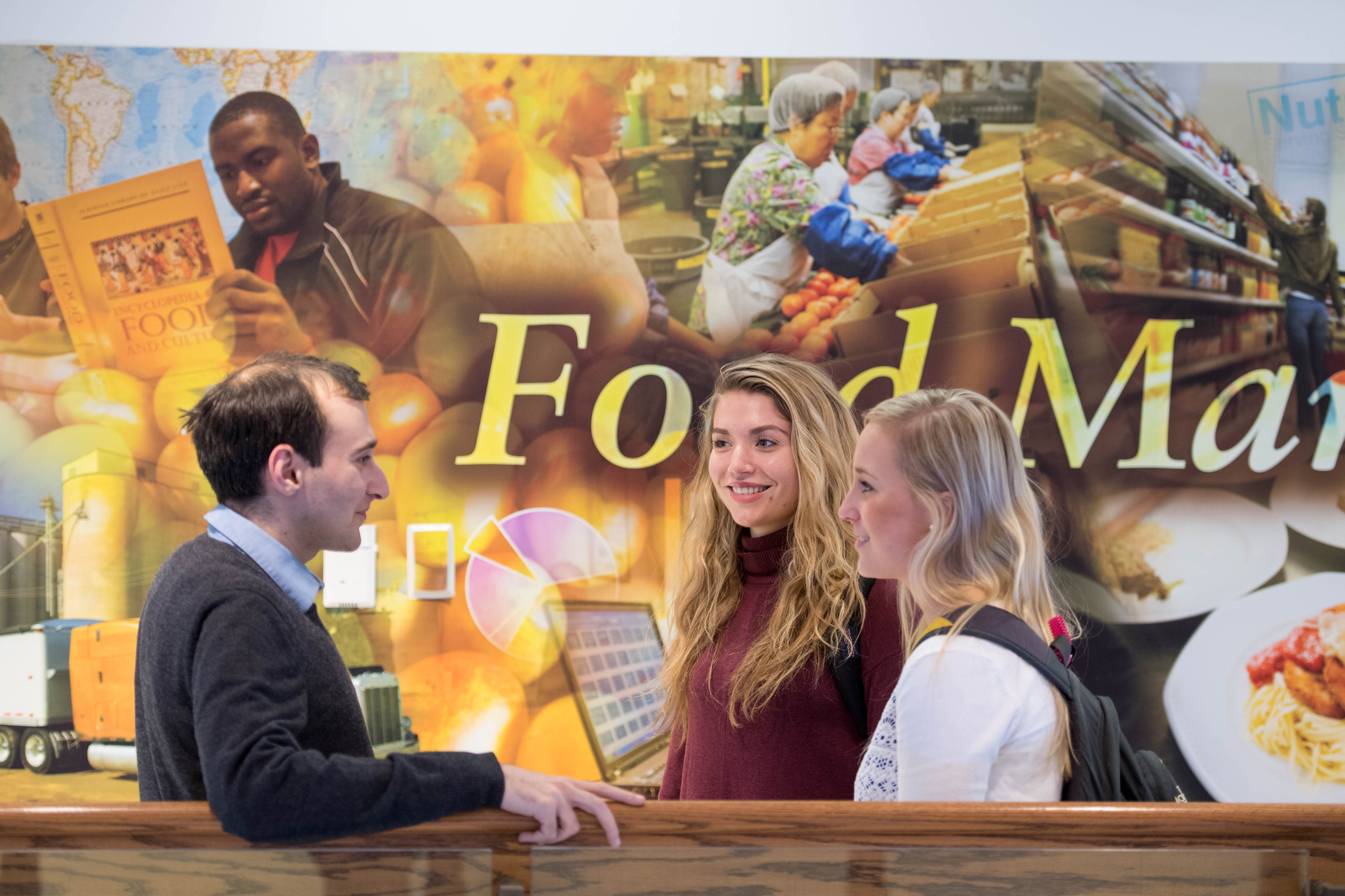 Students talk with professor Ernest Baskin, Ph.D., in front of the food marketing mural in Mandeville Hall