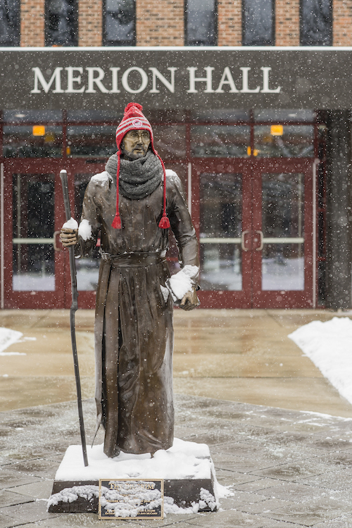 St Ignatius statue with a winter hat on as it snows