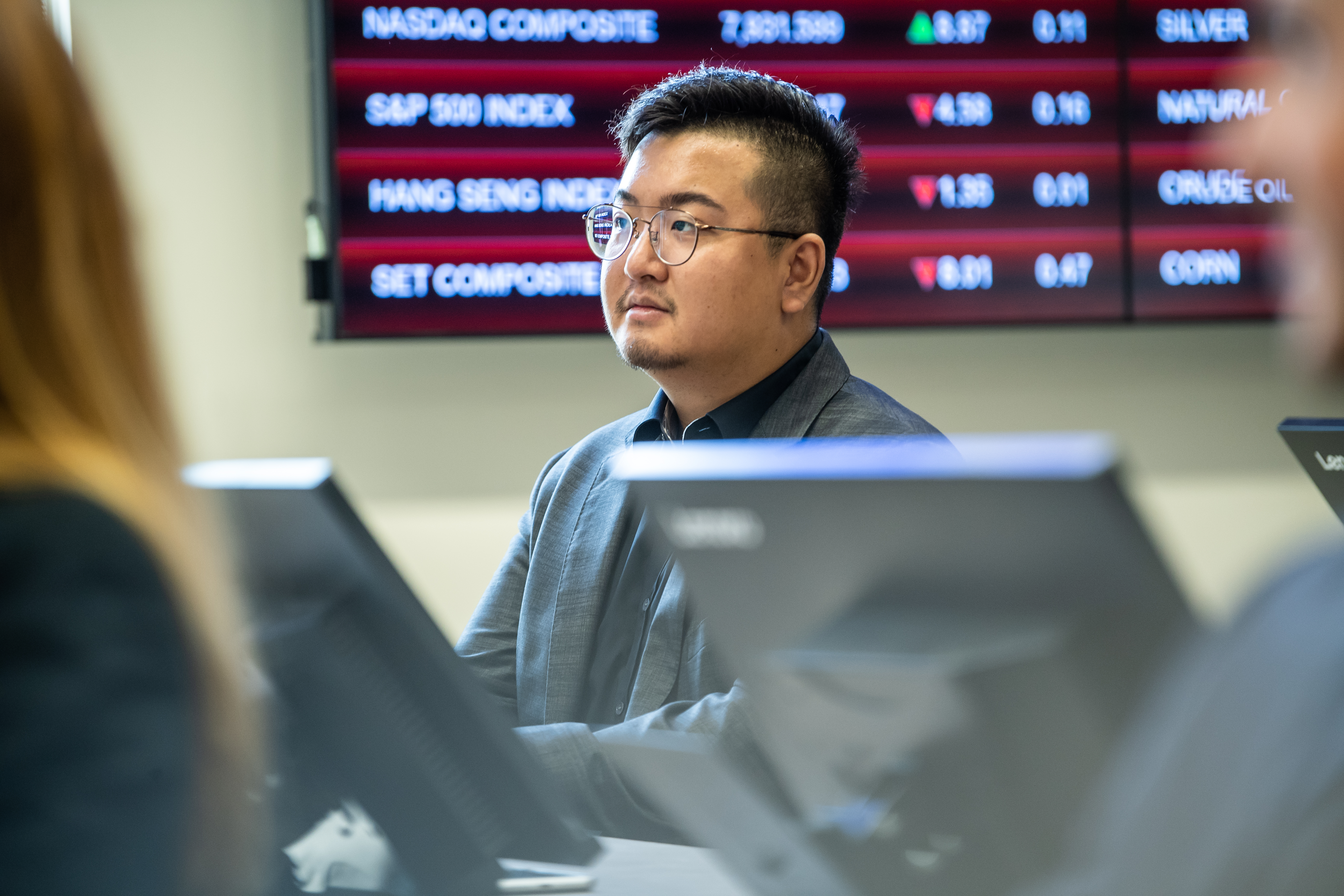 A student in Haub School's Wall Street Trading Room sits at a desk with eyes facing forward