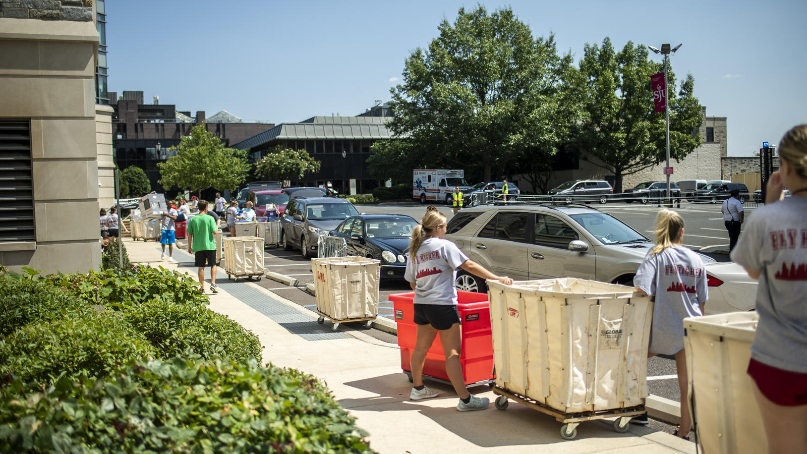 Students move big containers on wheels to help new freshmen move in.