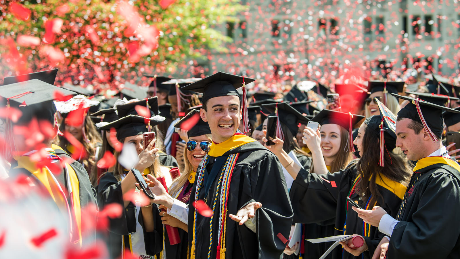 A graduate stands at commencement while confetti falls around him