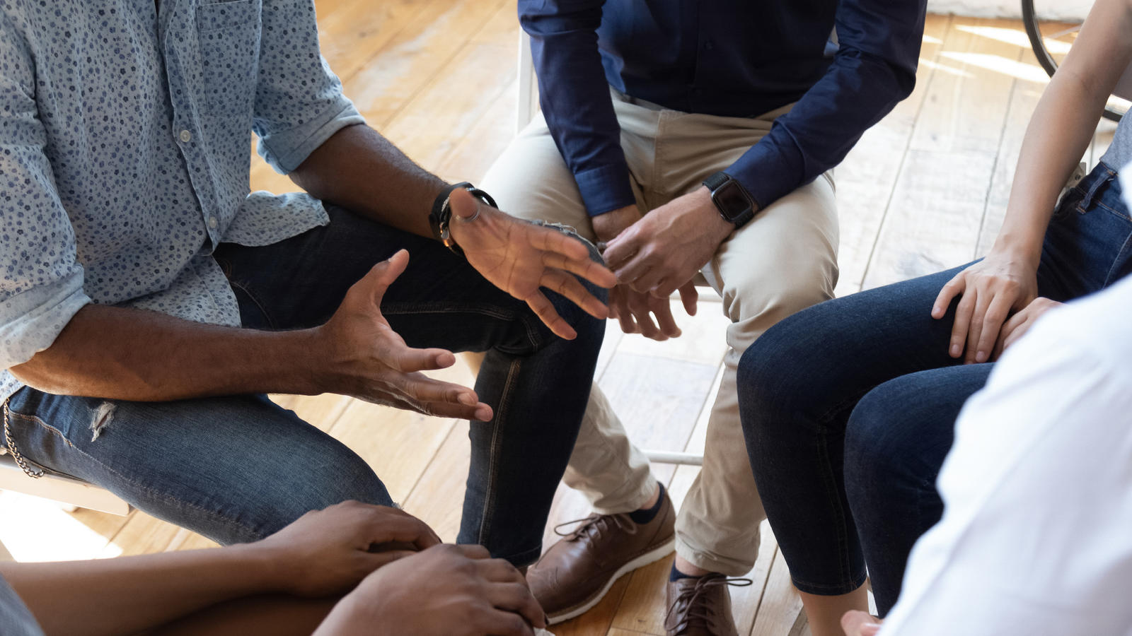 A closeup of hands in a circle, perhaps in a recovery group meeting