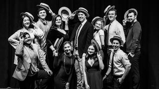 "The cast of ""Company"" poses in a vaudeville pose with boater hats."