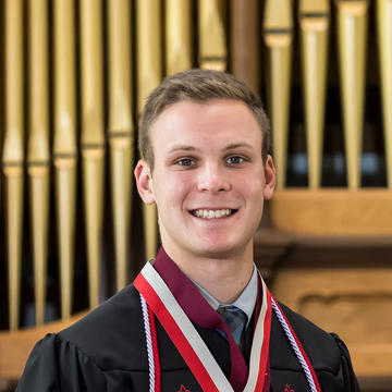 Andrew smiles in his graduation robes in the Chapel of Saint Joseph on campus