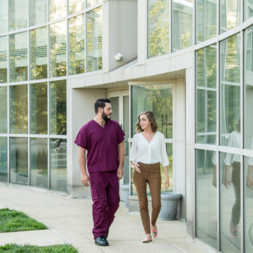 A young man in scrubs and a young woman in professional clothing walk across campus