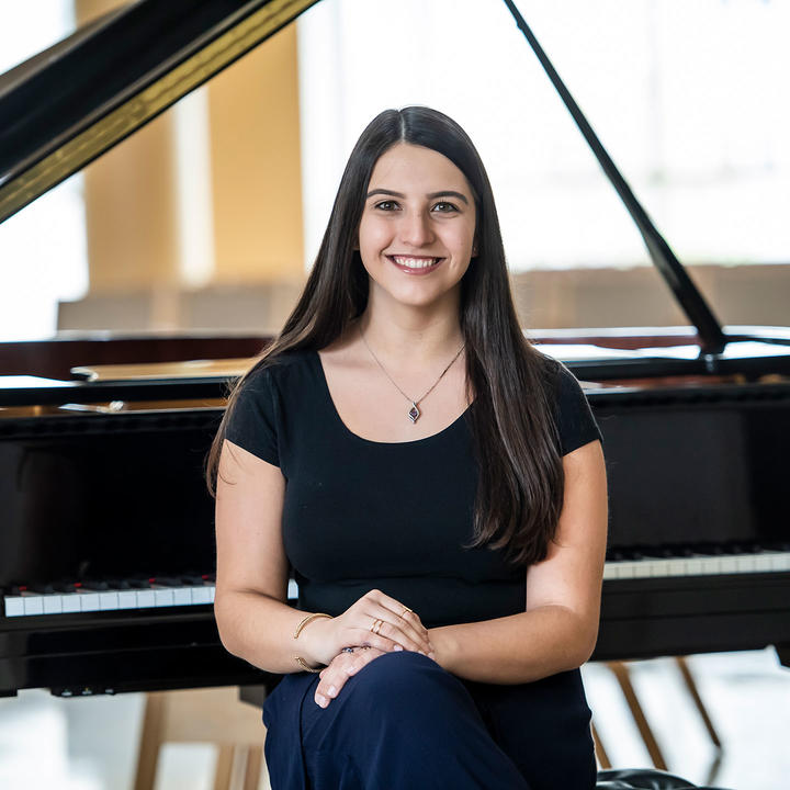 Olivia Centonza sitting in front of a piano