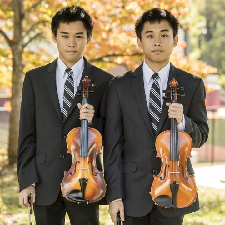 Dustin and Dylan Dinh, twins who are holding violins outside