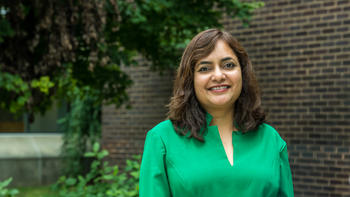 Usha Rao smiles wearing a green top in front of foliage and a brick wall