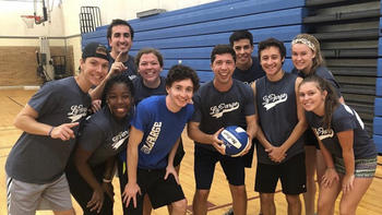 a group of students pose with a volleyball on a court