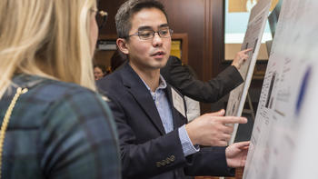 A student explains his research at a poster session